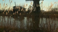 A slow tilt up to windmills standing along a canal in Holland. Stock Footage