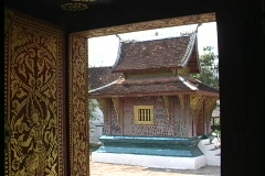 A small Buddhist temple seen through a doorway in Asia. Stock Footage