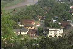 A aerial view of a small religious community near a river and forest in Laos. Stock Footage