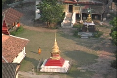 Buddhist Monks walk around a courtyard in an Asian community, in this birds-eye Stock Footage