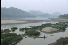 A beautiful view of a river in Asia with fishermen in longboats, and majestic Stock Footage