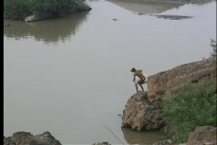 A birds-eye view of a fisherman casting his net on the water in Asia. Stock Footage