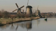 A boat moves along a canal in Holland with windmills nearby. Stock Footage