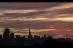The San Francisco skyline is silhouetted by a darkening sky. Stock Footage