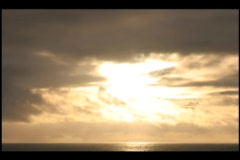 Time-lapse of fast moving clouds passing over water in a golden sky. Stock Footage