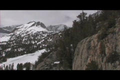 Snowy, rugged mountains rise behind rocky bluffs in a wilderness area. Stock Footage