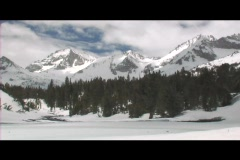 Rugged mountains rise behind a frozen lake in a wintry wilderness area. Stock Footage