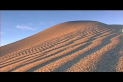 Golden light shines on sand dune furrows. - stock footage