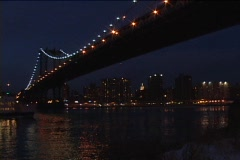 A passenger boat sails beneath a bridge at night. Stock Footage