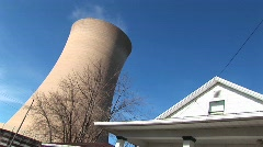A nuclear reactor looms above the roof of a white house Stock Footage