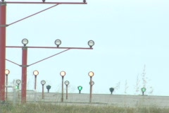 A jet plane comes in for a landing over landing lights during the day. Stock Footage