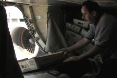 An employee grabs boxes from a conveyor belt and stacks them into the cargo hold Stock Footage