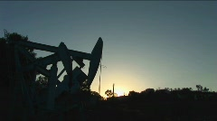 An oil well derrick is silhouetted against a glowing sky. Stock Footage