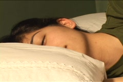 Time-lapse of sleeping woman reacting to light shining on her face; as her eyes Stock Footage