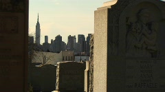 Headstones in a cemetery with the modern-day Manhattan skyline - stock footage
