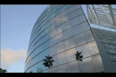 A shiny contemporary building reflects fast moving clouds in a blue sky. Stock Footage