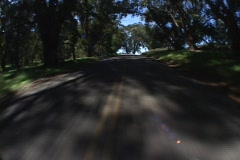 Point-of-view shot traveling down a narrow highway with shadows from trees. Stock Footage