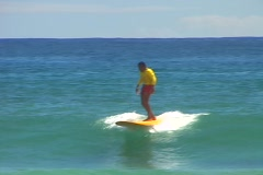 Surfer dressed in bright red and yellow runs out of wave and spills into the Stock Footage