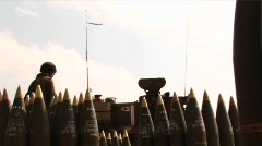 An army solider in Iraq stands amongst shells as a tank gun fires, - stock footage