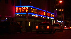 Cars pass by the brightly lit Radio City Musical Hall marquee Stock Footage