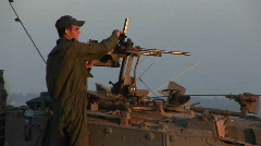 An Israeli soldier stands on a tank during a standoff at the Stock Footage