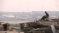 An Israeli army soldier sits atop a tank at the Gaza Strip border. Stock Footage