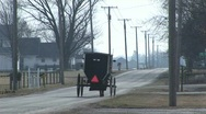 An Amish horse and carriage travel along a quiet country road Stock Footage