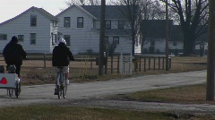 Two young people on bikes pull two very young kids in a child carrier Stock Footage