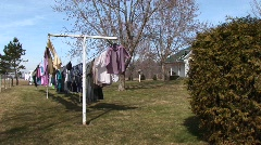 Clothes are hung on an outdoor clothesline to dry in the sunshine Stock Footage