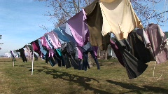 Colorful clothes hang on an outdoor clothesline to dry Stock Footage