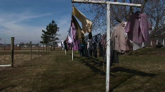 Colorful laundry hangs outdoors to dry in a rural community Stock Footage