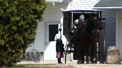 An Amish boy and girl prepare to travel via their horse and buggy Stock Footage