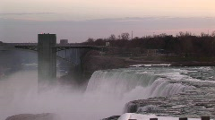 A moody view of Niagara Falls and bridge during golden-hour Stock Footage