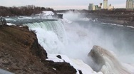 Stock Video Footage of Niagara Falls in winter with tourist hotels in the distance