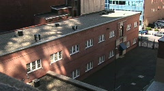 A low, non-descript, brick building is located in the city Stock Footage