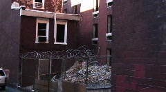 A cyclone fence and barbed-wire surrounds an abandoned building Stock Footage