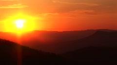 Pan left  across a fiery golden-hour sky above a mountain range Stock Footage