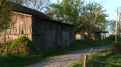 An old barn next to a dirt road with house in the background Stock Footage