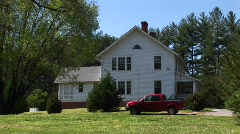 A red pickup sits parked in front of a quaint white farmhouse Stock Footage