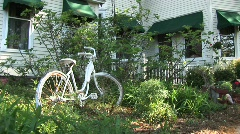 A bike sits in the bushes in front of a double story white house Stock Footage