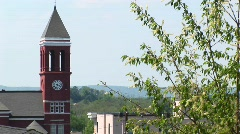 Treetop branches sway in the wind in front of an old clock tower Stock Footage