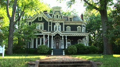 A lovely old house is surrounded by large leafy green trees Stock Footage
