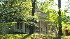 A medium-shot of a lovely old white house hidden in the trees Stock Footage