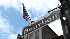 An American flag flies above a street sign identifying Bourbon Street - stock footage