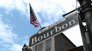 An American flag flies above a street sign identifying Bourbon Street Stock Footage