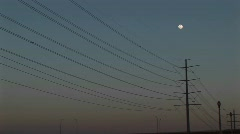 Long-shot the full moon hanging above power lines Stock Footage