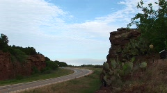 Cars driving on a highway next to a rocky outcropping in Texas Stock Footage