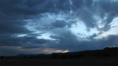 Pan-right shot of storm clouds over a hilly landscape Stock Footage