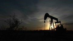 Medium shot of an oil pump turning in the New Mexico desert Stock Footage