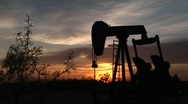 Stock Video Footage of Medium shot of a silhouetted oil pump turning in the New Mexico